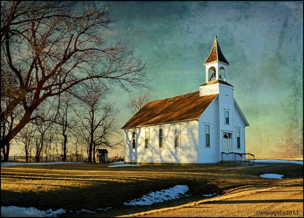 Small white wooden church at sunset.  Barren trees to the left, traces of snow on the ground,